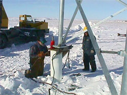 A welder secures the leg of a wind generator tower to a Helix-Pile at KEA's wind farm in Kotzebue, Alaska (Photo courtesy Kotzebue Electric Association)
